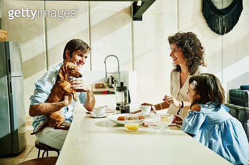 Smiling father holding dog while having breakfast with family in kitchen - gettyimageskorea