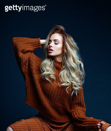 Fashion portrait of long hair blond young woman wearing brown sweater and skirt. Studio shot against black background. - gettyimageskorea