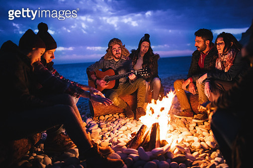 Young hipster friends with a guitar singing around a campfire at a beach at dusk - gettyimageskorea