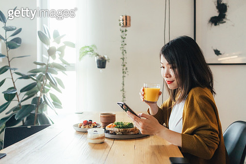 Young beautiful woman using phone while having breakfast - gettyimageskorea