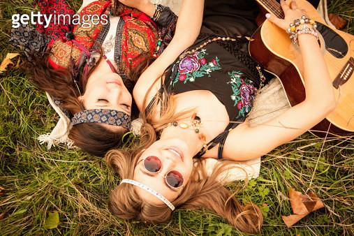 Hippy girls lying in field with guitar - gettyimageskorea