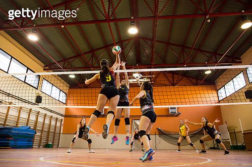 Volleyball player spiking the ball during a volleyball match - gettyimageskorea