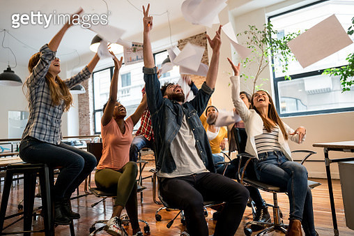 People celebrating at the office throwing papers in the air - gettyimageskorea