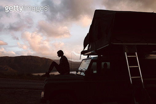 Woman sitting on a Jeep at Sundown - gettyimageskorea