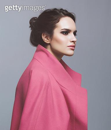 Studio portrait of young beautiful woman wearing pink coat - gettyimageskorea