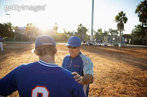 Coach talking with baseball player on sunny field - gettyimageskorea