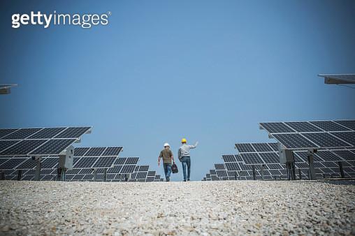 Caucasian technicians talking near solar panels - gettyimageskorea