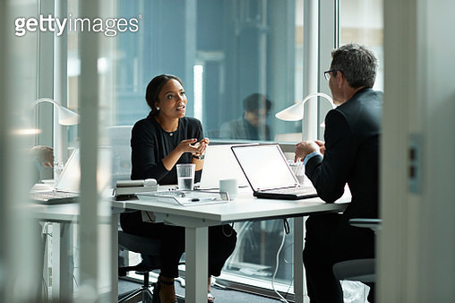 Businesswoman speaking with co-worker in open office - gettyimageskorea