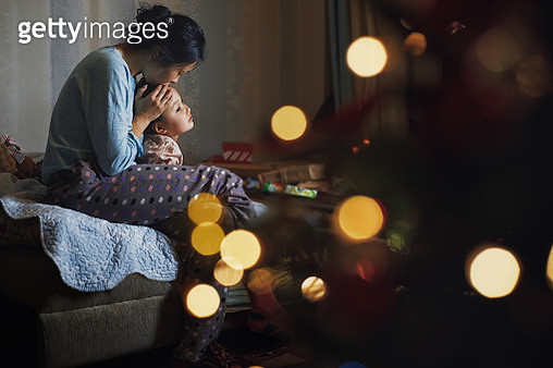 Mother kissing her daughter at home decorated for Christmas holiday - gettyimageskorea