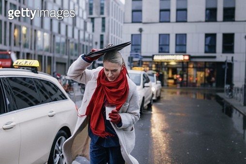 A businesswoman running on a busy street while sheilding herself from the rain with a folder. - gettyimageskorea