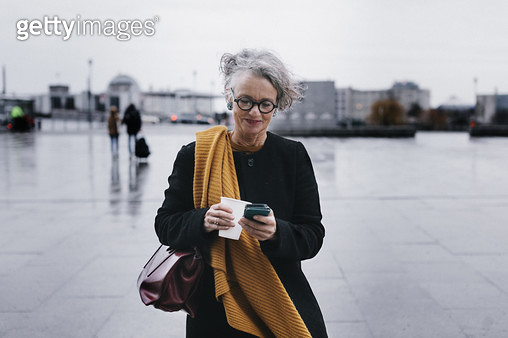 Businesswoman Smiling While Texting On Her Lunch Break - gettyimageskorea