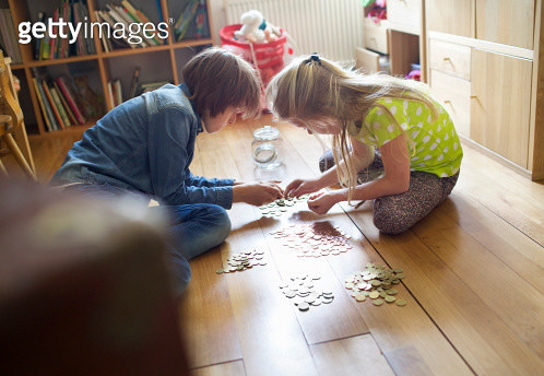 Brother and sister counting coins from savings jar - gettyimageskorea