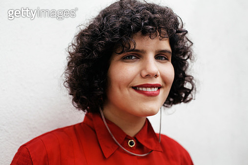 Close-up portrait of queer woman smiling and standing in front of a white brick wall - gettyimageskorea
