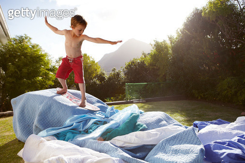 Boy, aged 6, pretending to surf a make believe wave in a suburban garden - gettyimageskorea