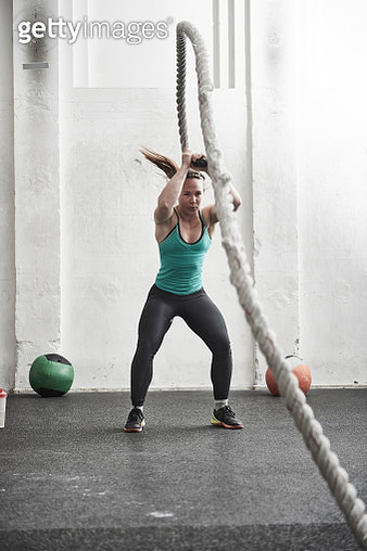 Woman working out with battle rope in cross training gym - gettyimageskorea