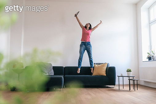 Woman at home with tablet jumping on sofa - gettyimageskorea