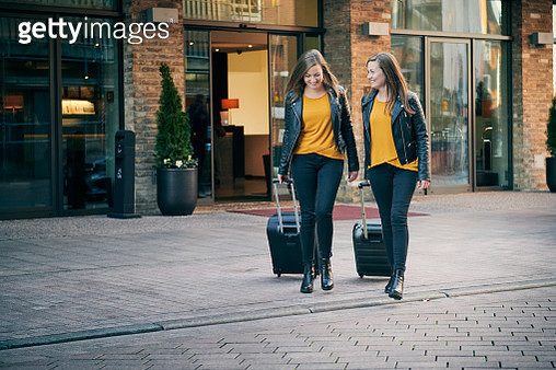 Two women with suitcases on city street - gettyimageskorea