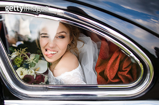 Beautiful bride shows tongue sitting in the car - gettyimageskorea