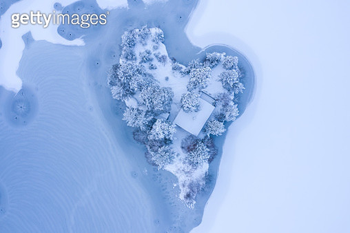 This image show a small island shaped like a heart with a single cottage. The surrounding lake and trees are covered in snow and thin ice. This lake is called Hagatjern, and is located in the outskirt of Drammen city, Norway. This image was taken with a d - gettyimageskorea