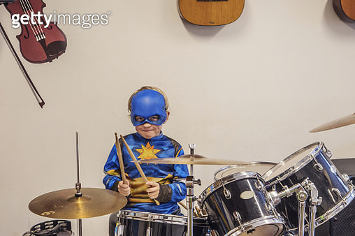 Seven year old boy in costume playing drums - gettyimageskorea