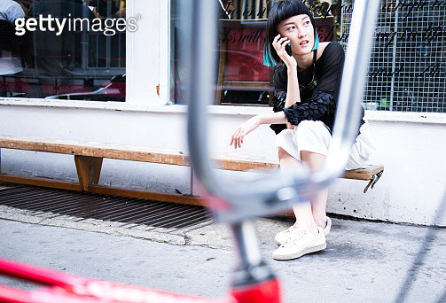 Young stylish woman sitting outside shop making smartphone call - gettyimageskorea
