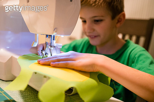 Young boy learns to sew on an electric sewing machine - gettyimageskorea