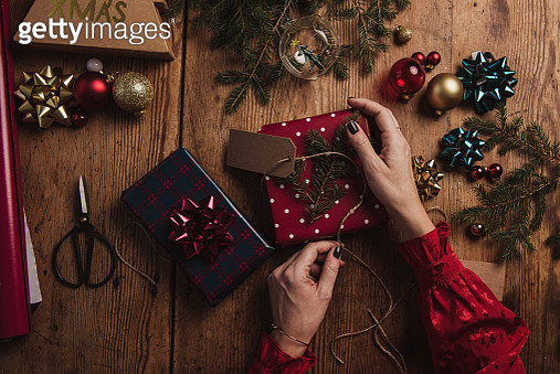 Woman wrapping christmas presents from above overhead table top shot - gettyimageskorea