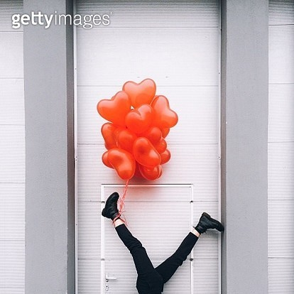 Low Section Of Woman With Red Heart Shape Balloons Against Door - gettyimageskorea