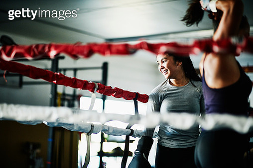 Smiling female boxer working out in boxing ring in gym - gettyimageskorea