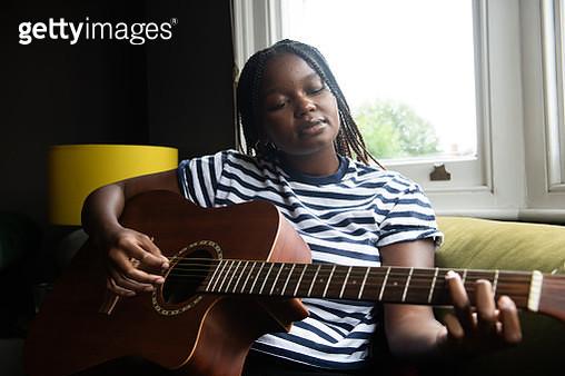 Teenage girl playing her guitar - gettyimageskorea