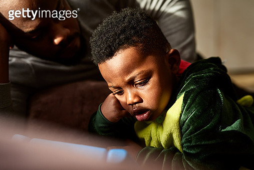 Close up of father and son on sofa watching screen, curiosity, connections, obsession - gettyimageskorea