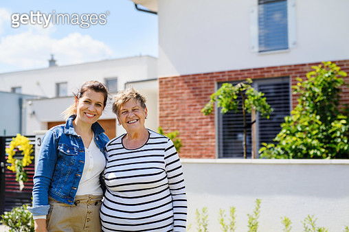 Portrait of woman with senior mother in backyard outdoors, looking at camera. - gettyimageskorea