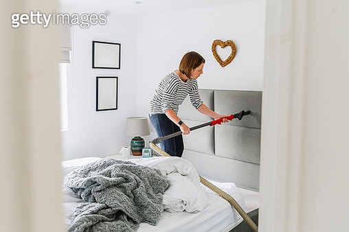 Woman deep cleaning her bedroom - gettyimageskorea