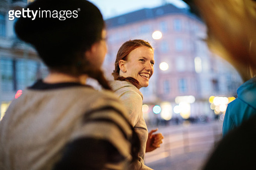 Smiling sporty woman with friends jogging on city street - gettyimageskorea