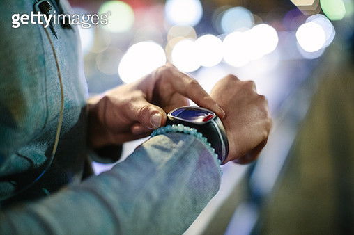 Sporty woman checking time on smart watch - gettyimageskorea