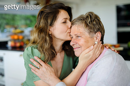 Portrait of woman with senior mother indoors at home, kissing. - gettyimageskorea