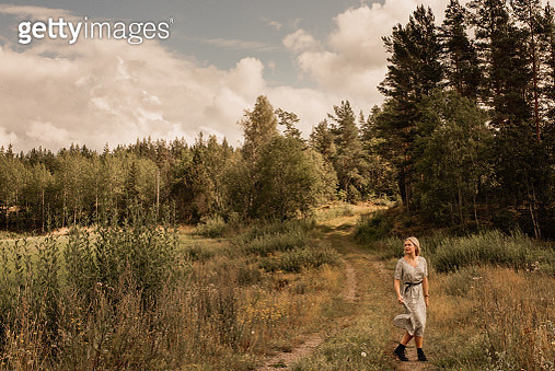 woman in forest woods contemporary modern woman wearing dress and boots in late summer autumn in the nature. - gettyimageskorea