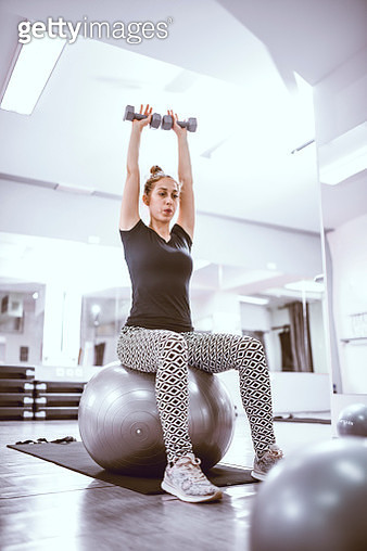 Fit Girl Is Exercising On a Pilates Ball In a Gym - gettyimageskorea