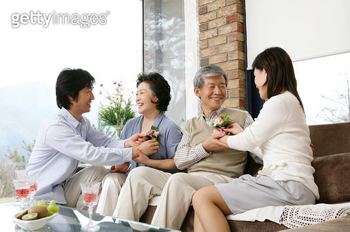 Parents receiving flower from son and daughter on parent's day, smiling - gettyimageskorea