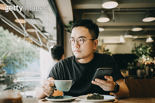 Smart young Asian man using smartphone and having coffee in cafe - gettyimageskorea