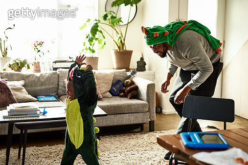 Father and son dressed as dragons playing in living room - gettyimageskorea