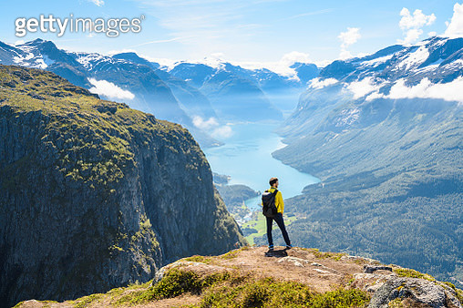 Tourist admiring the view from the top of a mountain in Loen, Norway - gettyimageskorea
