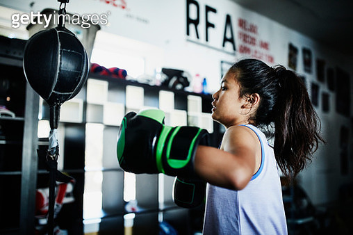 Young female boxer working on double ended bag in boxing gym - gettyimageskorea
