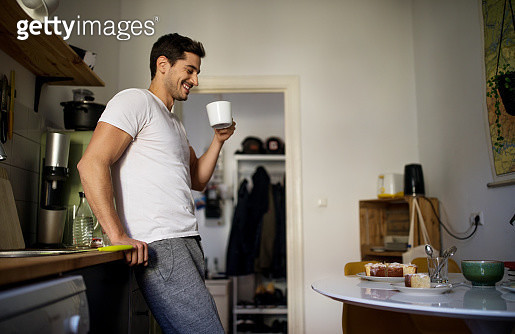Young man standing in kitchen and having coffee in morning at home - gettyimageskorea