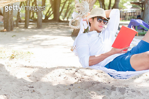 Young man reading in hammock on the beach in summer vacation. - gettyimageskorea
