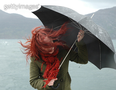Girl with umbrella and blowing hair - gettyimageskorea