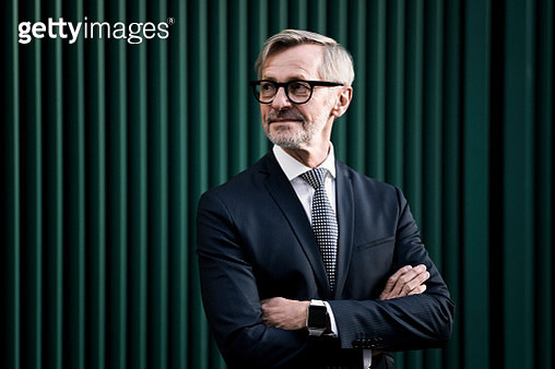 Portrait of grey-haired businessman in front of green wall - gettyimageskorea