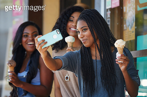 Girls taking selfies and eating ice cream - gettyimageskorea