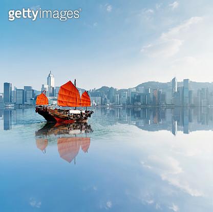 Junk boat crossing Hong Kong harbor - gettyimageskorea