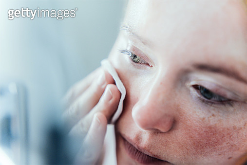Woman removing make up in bathroom. - gettyimageskorea